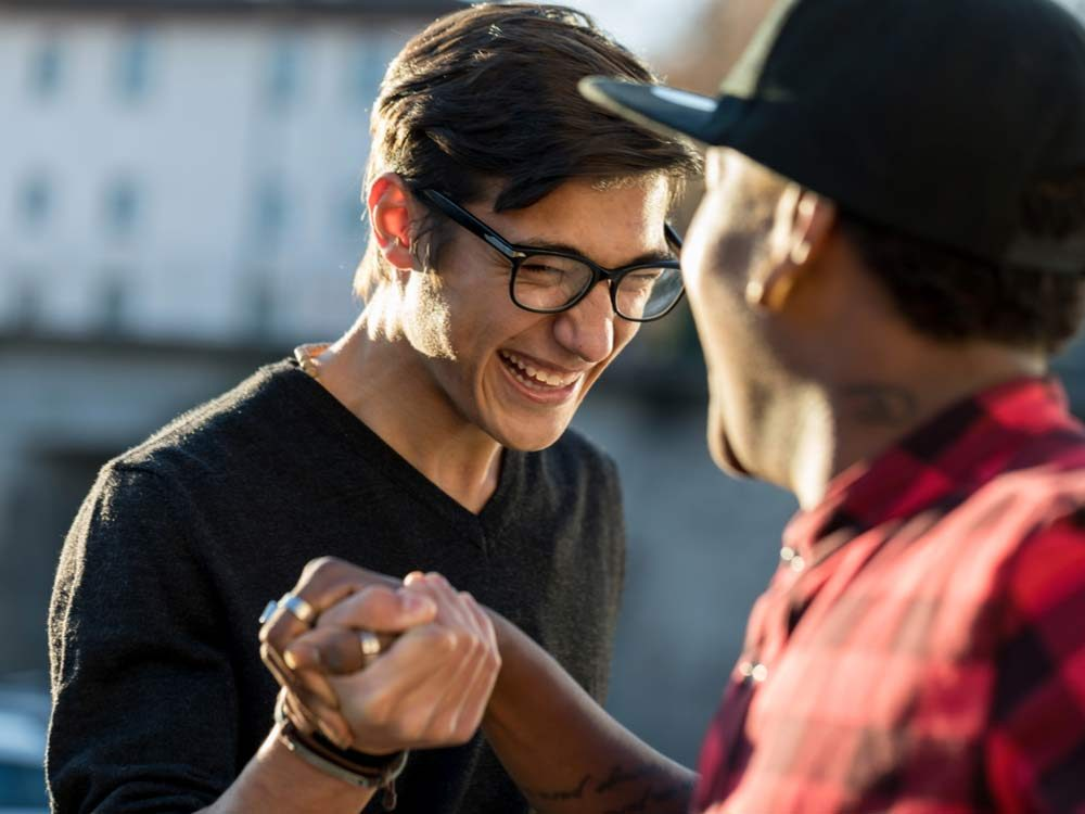 Two friends shaking hands while laughing