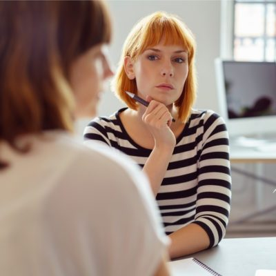 Female coworker suspicious of her colleague during team meeting