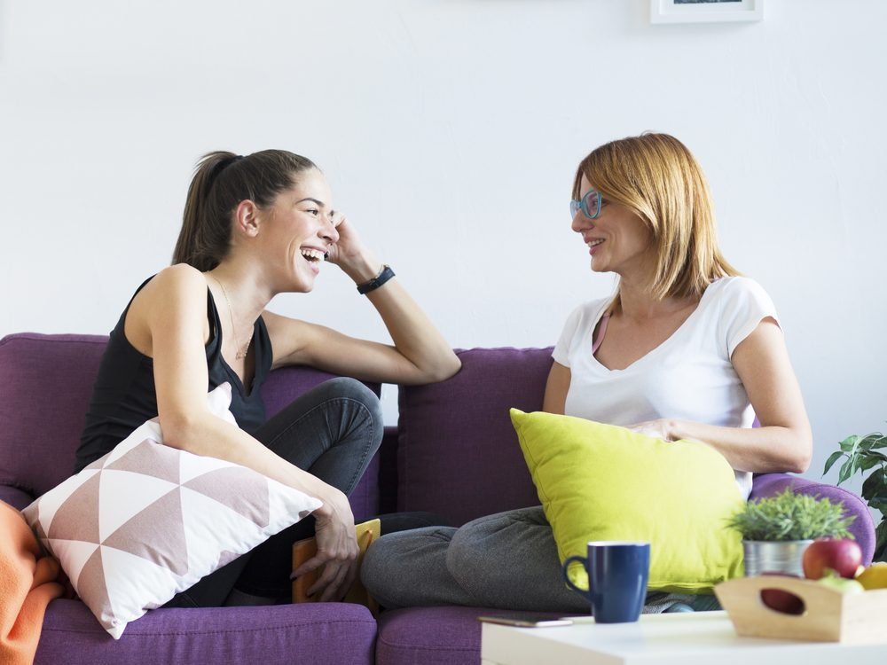 Two female friends talking on couch