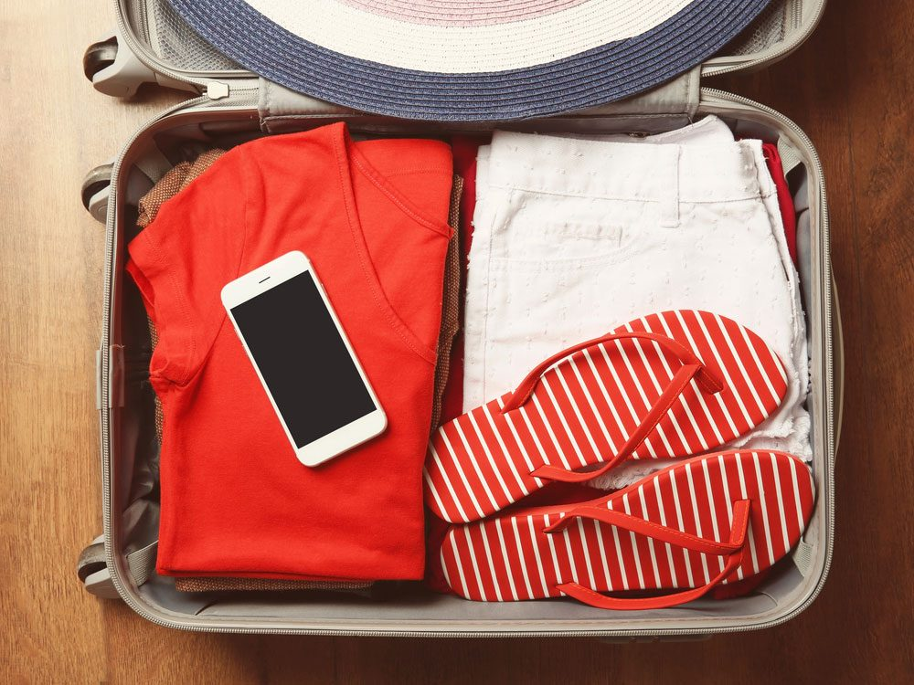 Open suitcase with female summer clothes