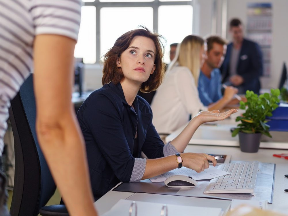 Young businesswoman in serious discussion with colleague