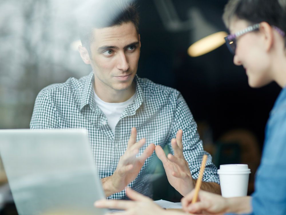 Young man sharing ideas with colleague in office