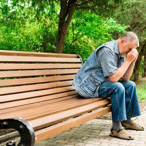 Testicular cancer symptoms - Depressed man on park bench