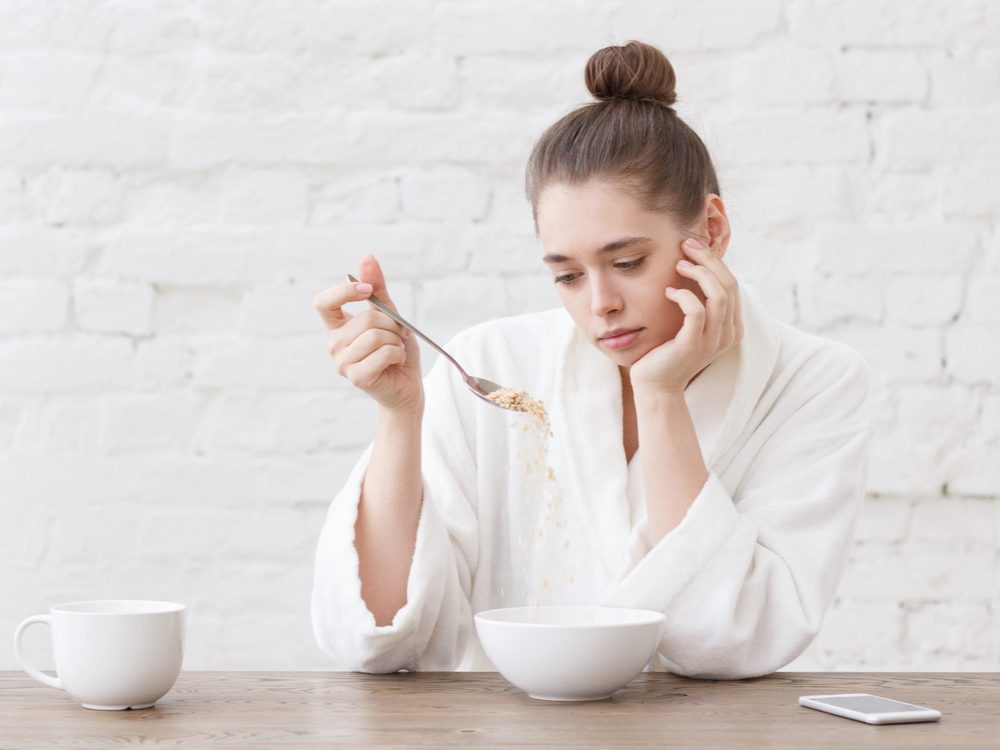 Woman looking sad, eating cereal in her kitchen