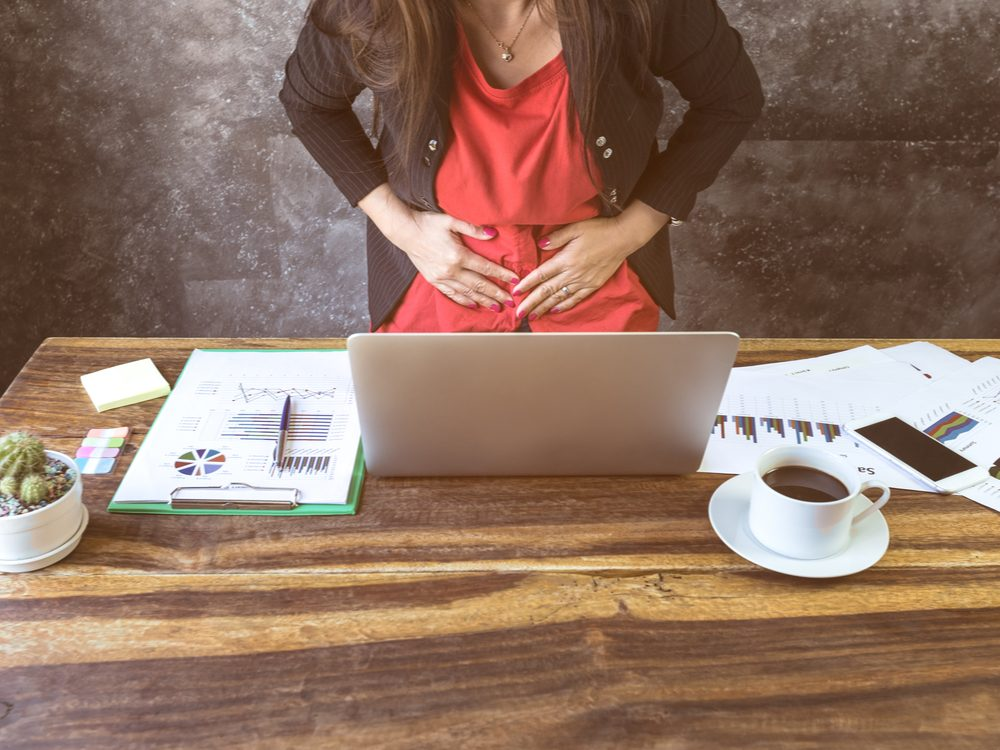 Woman at desk holding onto stomach