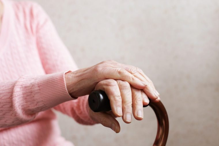 Elderly woman's hands holding walking cane