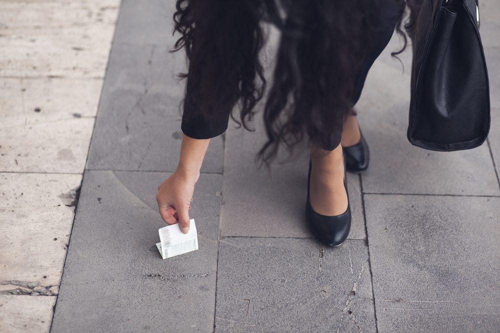 Picking up cash money off the sidewalk