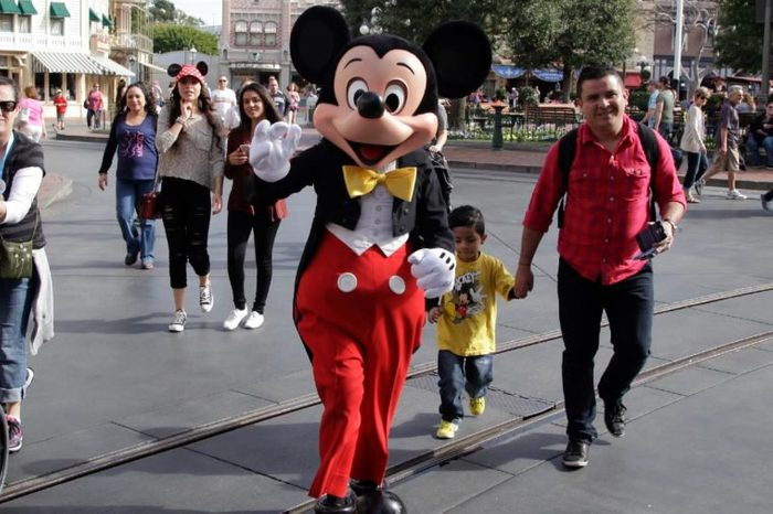 Visitors follow Mickey Mouse for photos at Disneyland, in Anaheim, Calif. Seventy people have been infected in a measles outbreak that led California public health officials to urge those who haven't been vaccinated against the disease, including children too young to be immunized, should avoid Disney parks where the spread originated