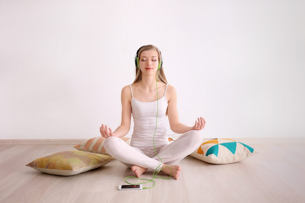Woman meditating while listening to music