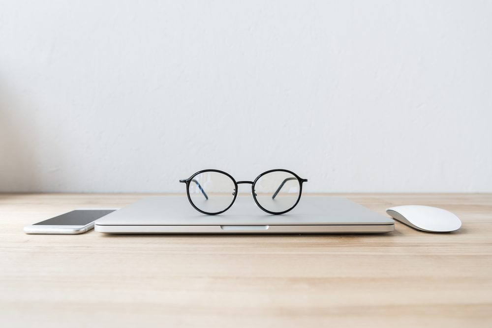 Round glasses and Mac laptop