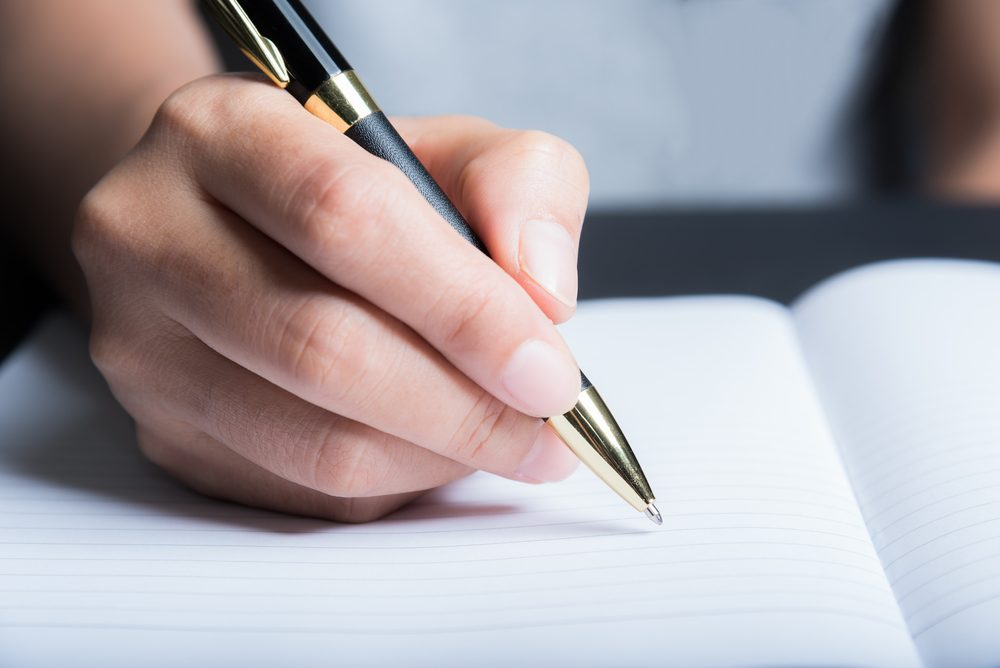Writing in notebook with pen