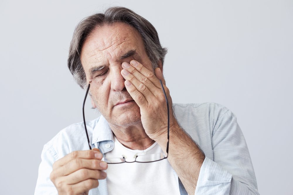 Middle-aged man rubbing his face