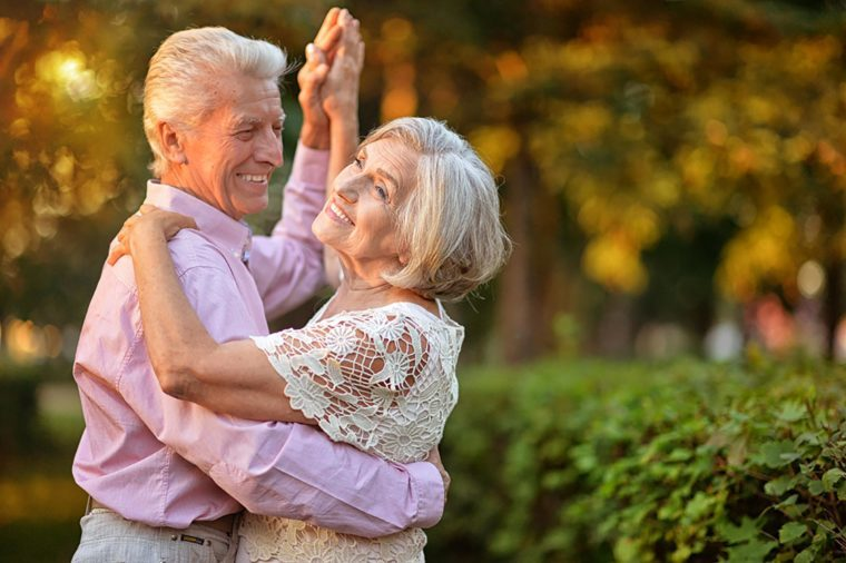 Senior couple dancing happily in garden