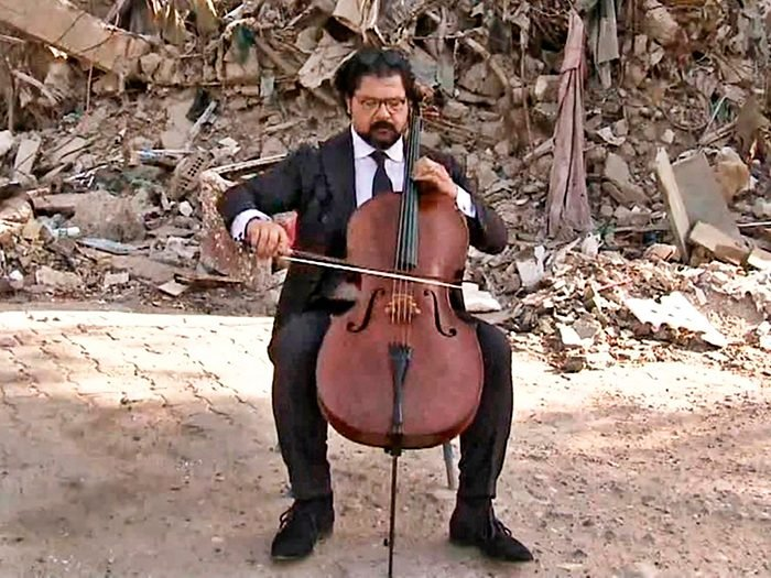 Karim Wasfi plays cello at the site of a car bombing