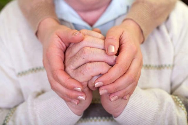 Close up picture of elderly hands with young caretaker's hands