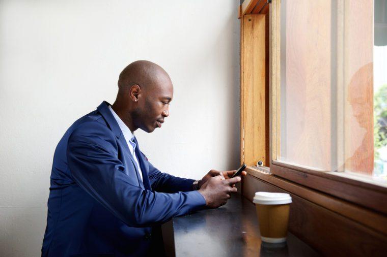 Man texting at cafe