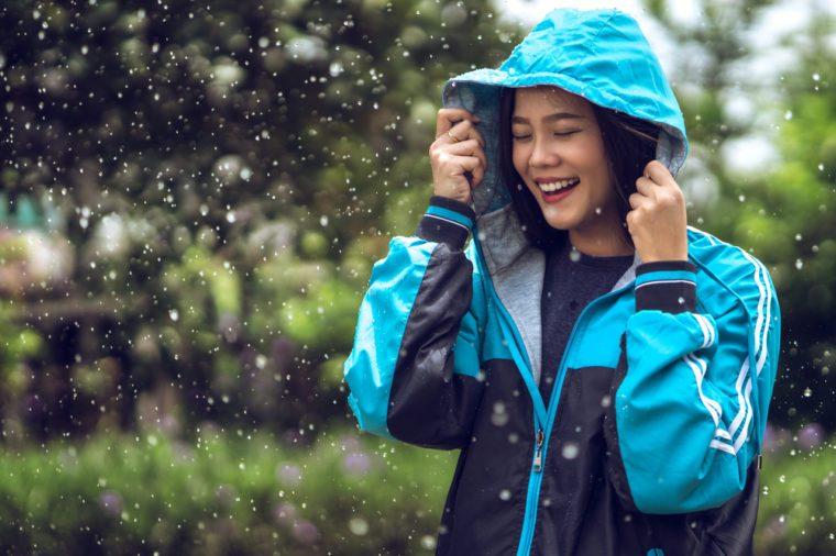 Hooded happy woman in the rain