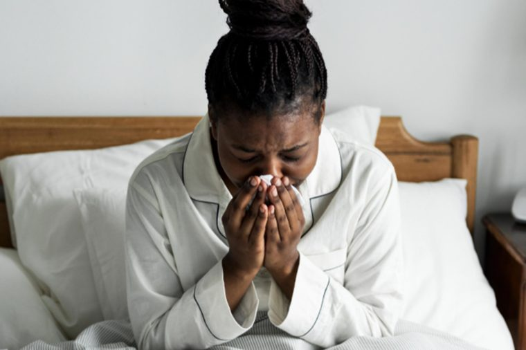 Black woman with allergies sick in bed
