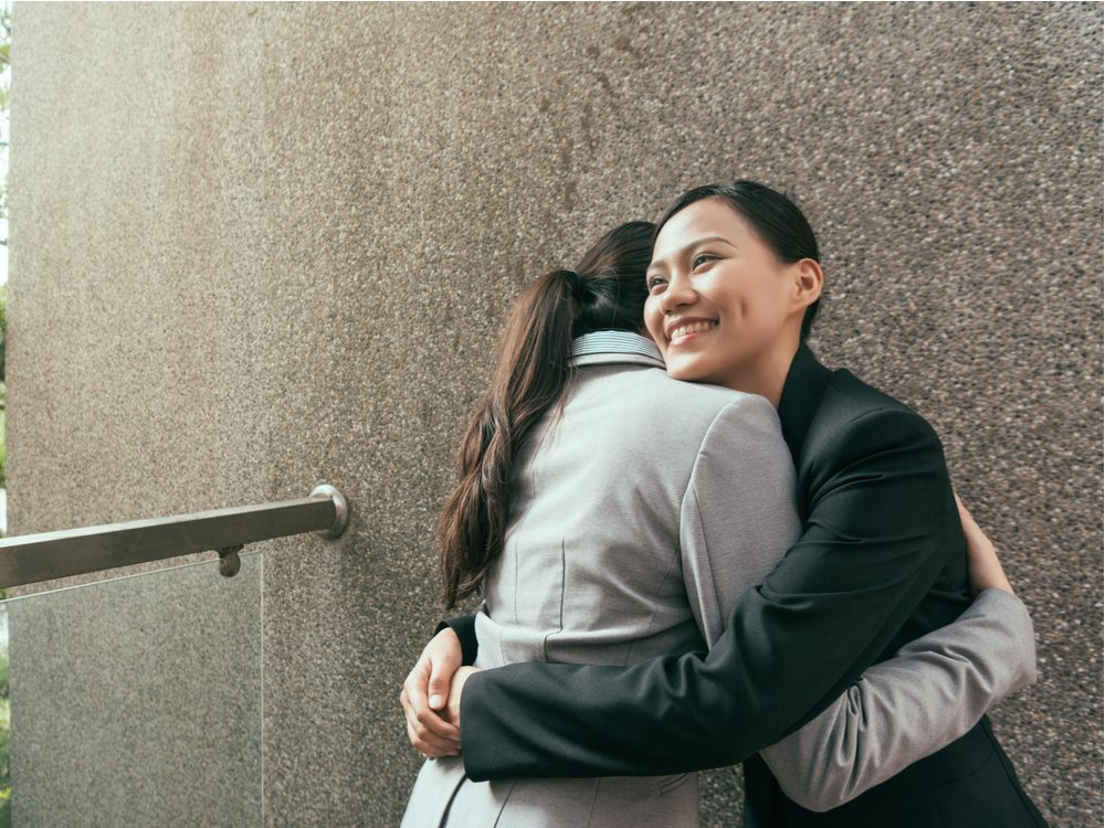Female coworkers hugging