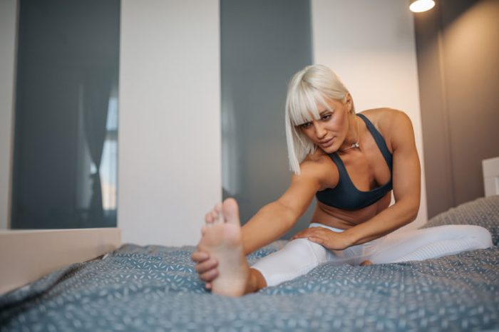 Young attractive woman stretching on her bed