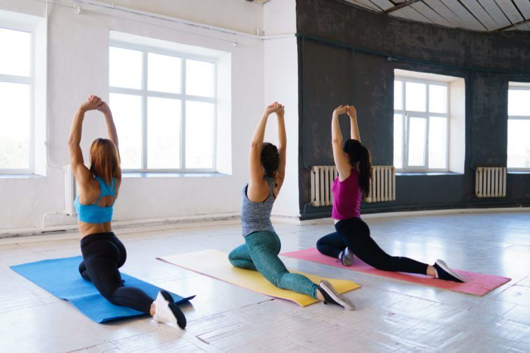 Yoga class, pilates, flexibility, health, fitness, correct posture and active lifestyle. Fit women doing stretching exercises preparing for splits.