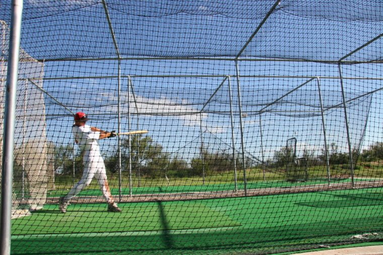 practicing hitting baseball in a batting cage