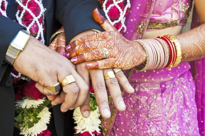 Horizontal color capture taken at a hindu wedding in Surat India. Photo session after the ceremony of the happy hand holding couple displaying their rings of matrimony and the bride lays her claim