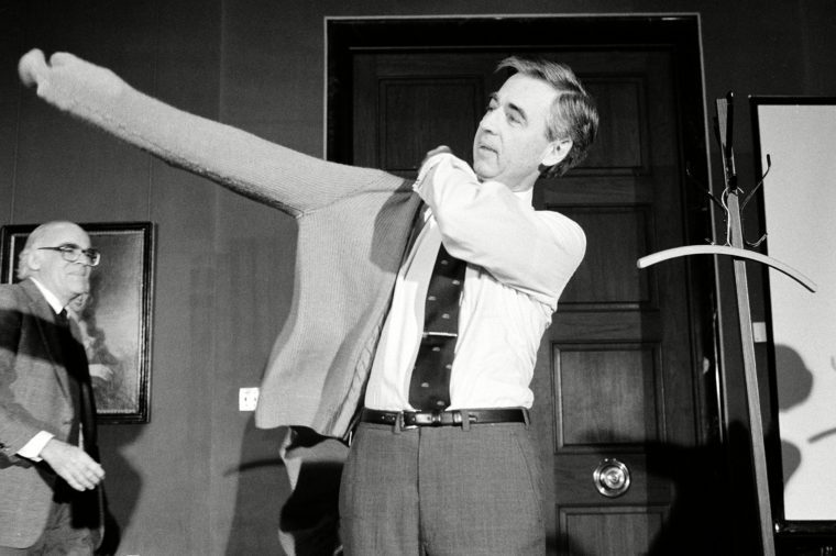 Fred Rogers putting on his trademark sweater