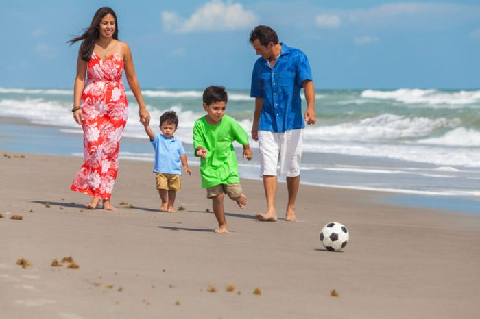 A happy family of mother, father parents & two boy son children, playng football or soccer and having fun in the sand of a sunny beach