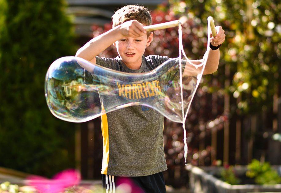 Little boy blowing bubbles outdoors