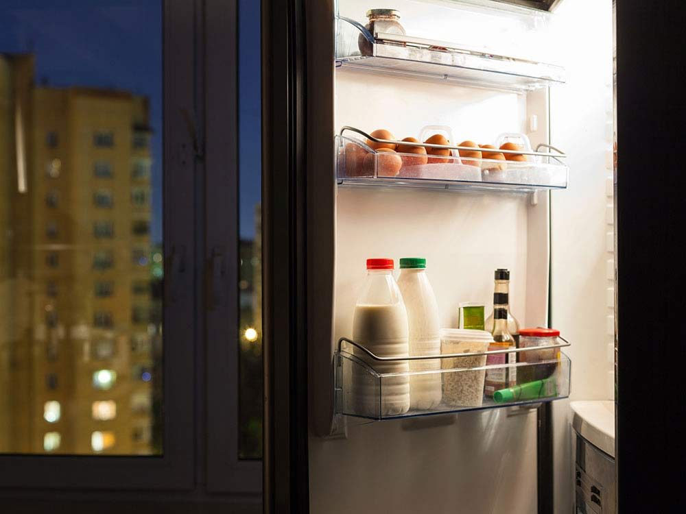 Open fridge door with eggs and dairy