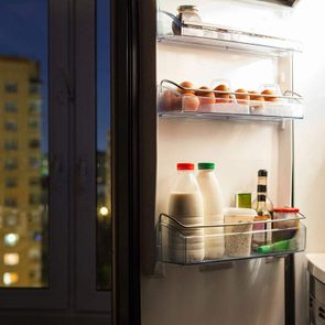 Open fridge door with eggs and dairy