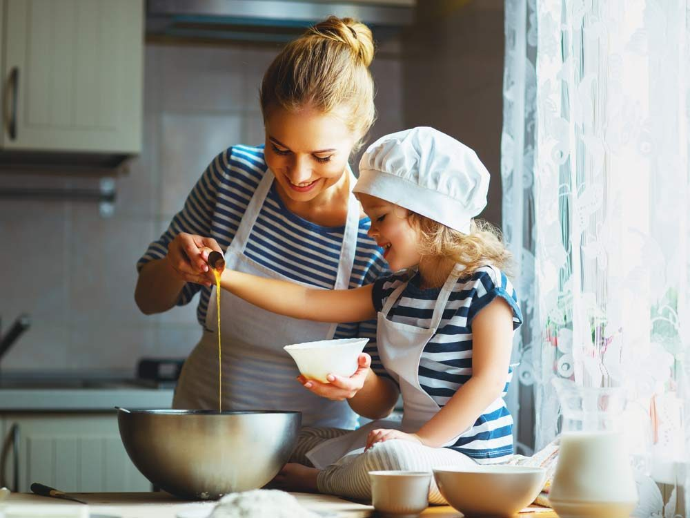 Young child making food in kitchen with her mother