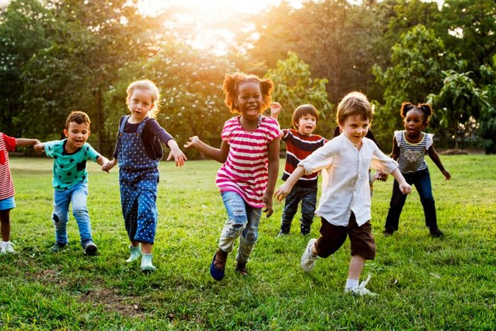 Little children playing in field at school