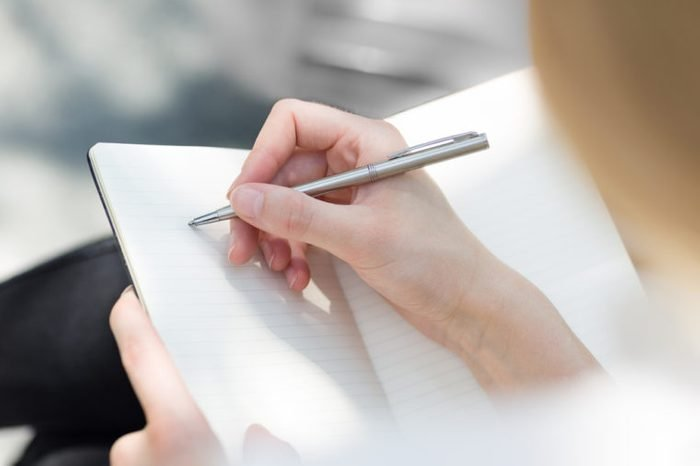 Close-up of a female hand writing on an blank notebook with a pen.