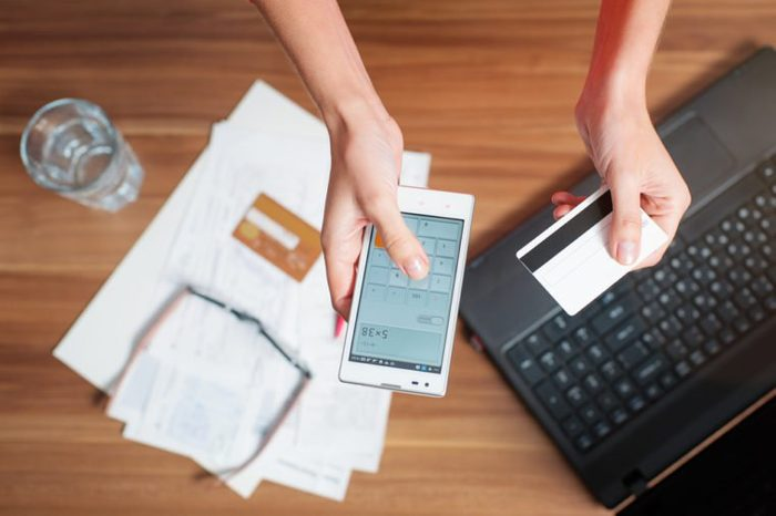 Business work place with female hands holding smart phone and bank card, top view