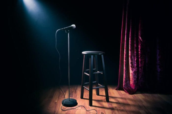 microphone and stool on a stand up comedy stage with reflectors ray, high contrast image