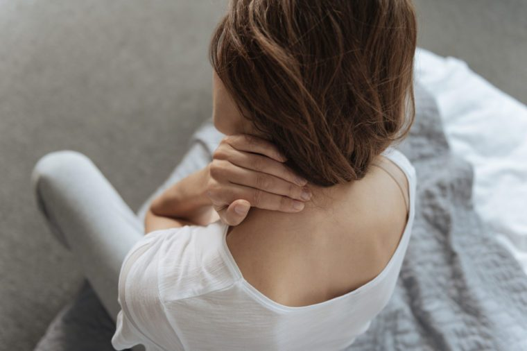 Unhappy young woman suffering from pain in the neck