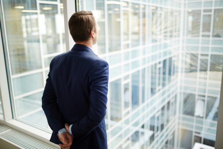Rear view of elegant businessman standing by window of new office and looking through it