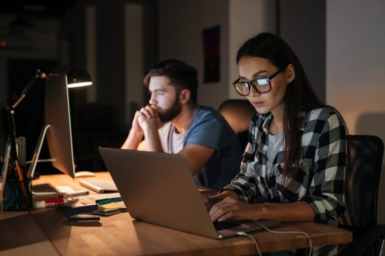 Image of two business people working with laptop and computer late at night in their office.