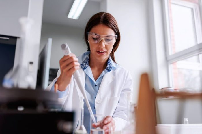 Woman scientist in laboratory doing chemical tests