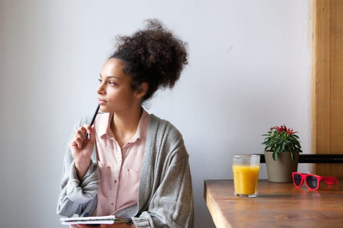 Portrait of a young woman sitting at home with pen and paper