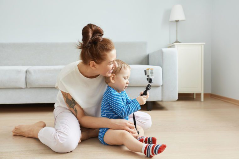 Sideways portrait of happy young Caucasian mother and son sitting at the floor at home, making selfie. Smiling woman in white clothes hugging her baby. Kid taking a picture with selfie stick.