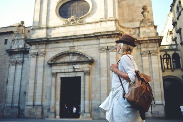 Back view of a young woman traveler with a backpack on her shoulder out sightseeing in a foreign city, stylish female foreigner examines architectural monument during her long-awaited summer vacation