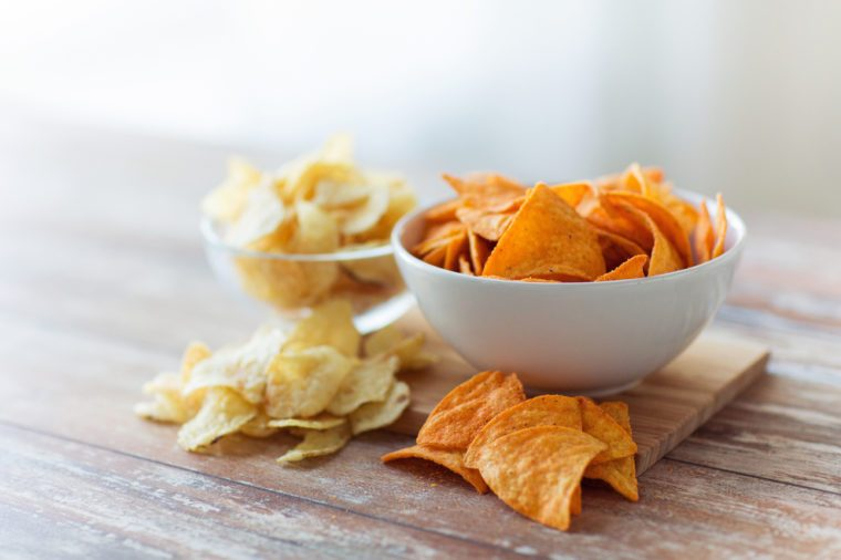 close up of potato crisps and nachos in glass bowl