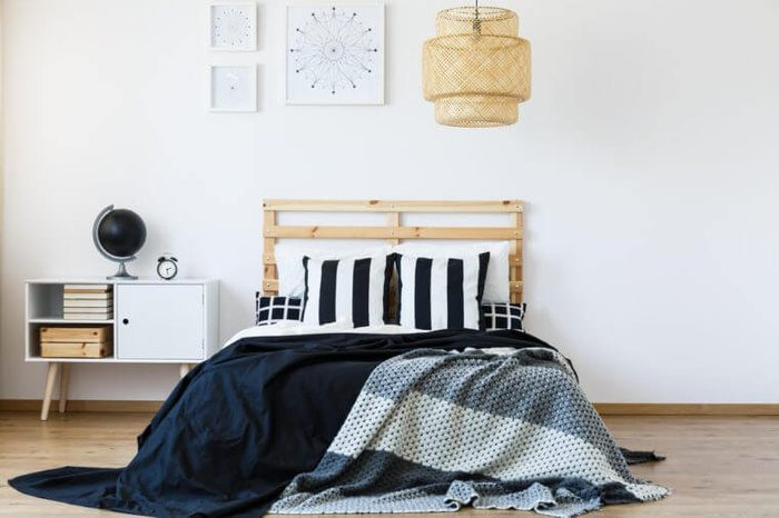 Comfortable bed with wooden headboard and black and white bedding