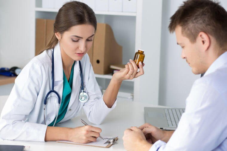 Female medicine doctor prescribing pills to her male patient. Healthcare, medical and pharmacy concept.