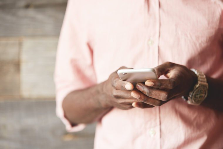 Internet addiction concept. Cropped shot of young African American blogger with stylish watches, holding smart phone while writing comments and posting new food photos on popular social networks