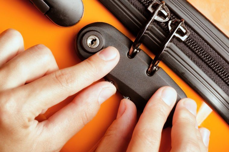 Woman locked her luggage in the orange suitcase.