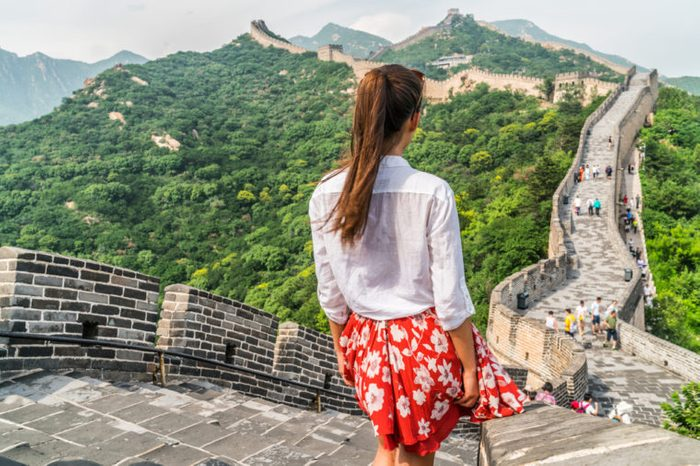 Young girl tourist from behind looking at view of Great Wall of China at famous Badaling tourism attraction during travel vacation in Beijing. Asia summer holidays.